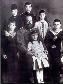 Black-and-white photograph of the Romanov family. Olga is a young girl who stands at the front resting against the arms of her seated bearded and bald father, who wears a military uniform. The older children and the empress complete the group.